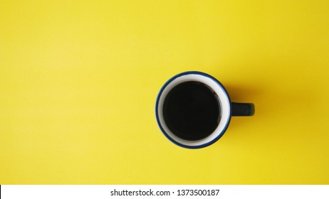 Top view of hot coffee on yellow background.