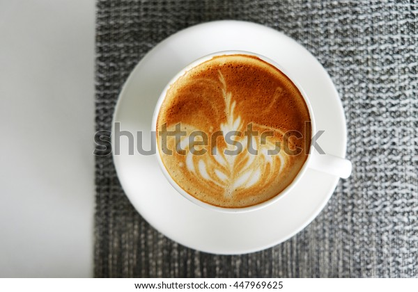 Top view of hot coffee on white table and napkin concept.