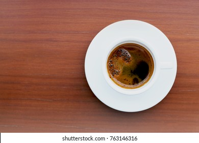Top view of hot espresso bombon in white ceramic coffee cup on wooden table background. Cafe Bombon is a type of coffee drink that includes espresso mixed with sweetened condensed milk.
