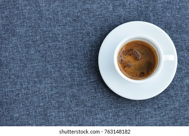 Top view of hot espresso bombon in white ceramic coffee cup on blue tablecloth background. Cafe Bombon is a type of coffee drink that includes espresso mixed with sweetened condensed milk.