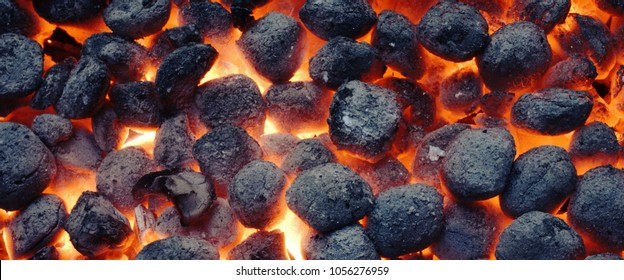 Top View Of Hot Flaming Charcoal Briquettes Glowing In The BBQ Grill Pit. Abstract Red Black Background, Texture Or Wallpaper. Burning Coals For Cooking Barbecue Food. Close Up. Web Banner