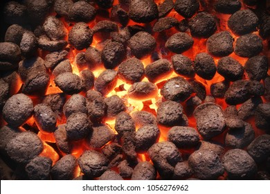 Top View Of Hot Flaming Charcoal Briquettes Glowing In The BBQ Grill Pit. Abstract Red Black Background, Texture Or Wallpaper. Burning Coals For Cooking Barbecue Food. Close Up.