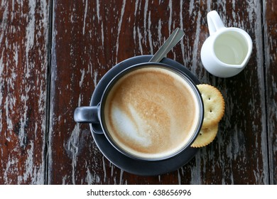 Top view - hot latte coffee with biscuit and syrup on wood background