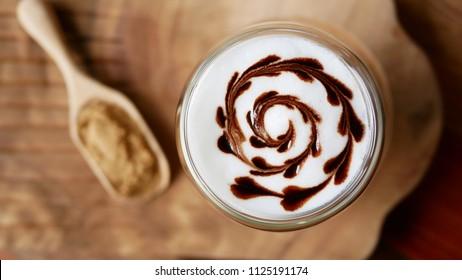 Top view of hot mocha coffee latte art chocolate heart shape spiral glass on table background, vintage style