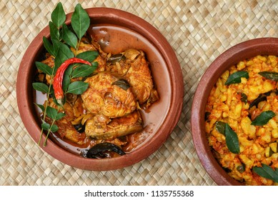 Top view of hot and spicy popular Kerala King or Barracuda fish curry made with coconut milk and tapioca or cassava in earthen ware,clay or  mud pot . South Indian dish favorite of tourists in Kochi