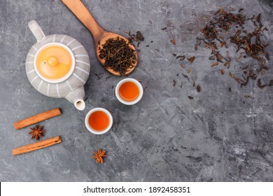 Top view of hot tea in a jug and in a teacup placed on a vintage table.