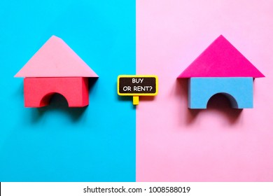 Top view of house model and blackboard written with ' BUY OR RENT?' on blue and purple background. Real estate,business and finance theme.