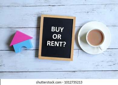 Top view of house model and blackboard written with ' BUY OR RENT?' with cup of coffee on white wooden background. Real estate,business and finance theme.