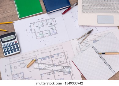 Top view of house plan with laptop, calculator and pencils