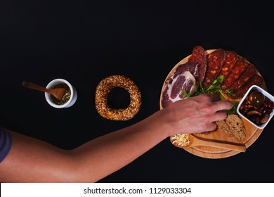 top view of human hand picking up a food from a wooden round plate. - Shutterstock ID 1129033304