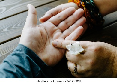 Top view of human hand and psychic or fortune teller explains lines on palm. Palmistry concept