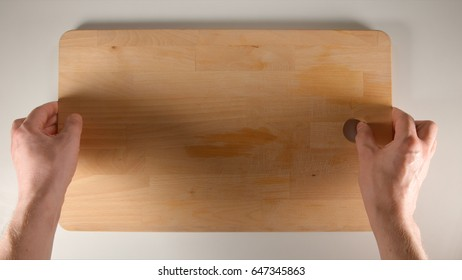 TOP VIEW: Human hands puts big cutting board on a white table