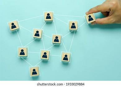 Top-Sicht auf Personalressourcen und Recruiting Business- oder Teamleiter-Konzepte. Hand erwachsenen asiatischen Mann halten Menschen Symbol Gemeinschaft auf hölzernem Würfel Block. Objekte auf blauem Hintergrund. Kopienraum .