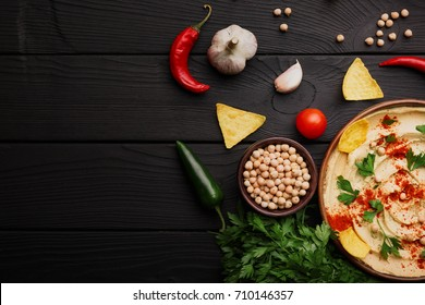 Top view of hummus ingredients. Yellow hummus and chips on a wooden background. Hummus preparation concept. Copy space.