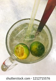 Top view of an ice cold calamansi drink in a clear glass cup with plastic straw and metal spoon sticking out of the cup.