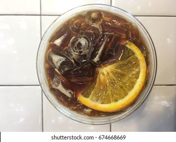 top view of Ice orange cold brews coffee on white tile background
