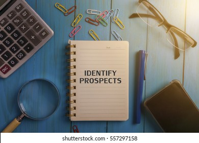 Top view of IDENTIFY PROSPECTS written on the notebook,magnifier glass,calculator,smart phone,pen and glasses on blue wooden desk.business concept.