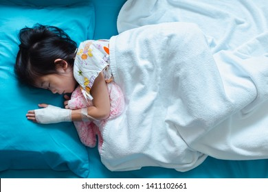 Top view. Illness asian child admitted in hospital with saline intravenous (IV) on hand. Girl sleeping at comfortable equipped hospital room. Health care stories.