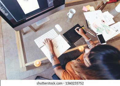 Top view of an illustrator making creative designs on a computer. Female artist using a digital writing pad to make an illustration on a computer.