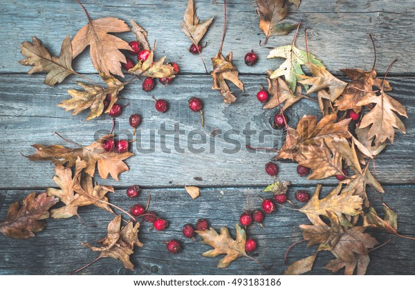 top view image of autumn leaves over wooden textured background