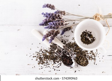 Top view image of back and green tea and lavender flowers over rustic background
