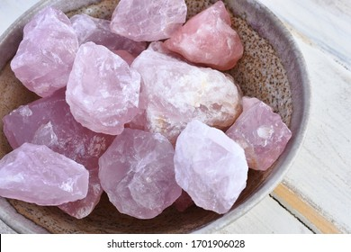 A top view image of a bowl of rose quartz healing crystals on a white table.