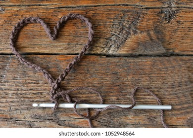 A top view image of a brown crochet heart shape.