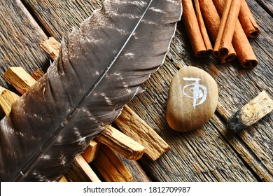 A top view image of a brown feather with various smudge sticks and reiki healing symbol.