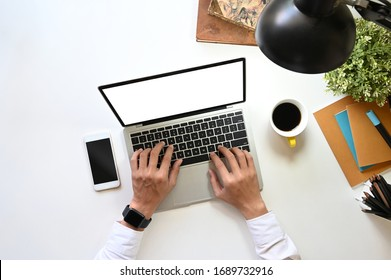 Top view image of businessman's hand typing on white blank screen computer laptop that putting on white working desk with office equipment. Orderly workplace concept.