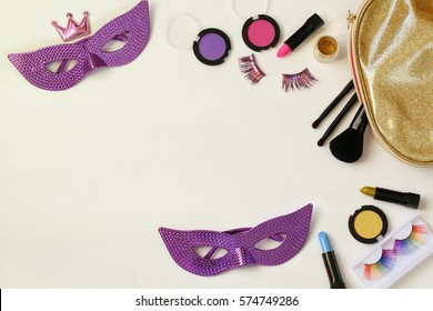 Top view image of carnival makeup on white wooden background