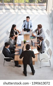 top view image of caucasian lecturer giving public presentation with company business graph result on white board in meeting room and multiethnic business people are paying attention (seminar concept