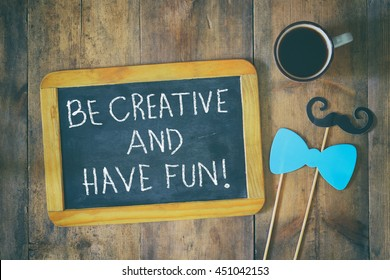 """top view image of chalkboard with the phrase """"be creative and have fun"""" over wooden table with photo booth accessories and cup of coffee. retro style filter"""