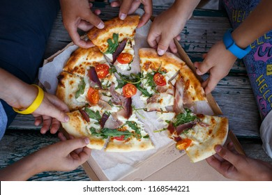 Top view image of children grab slices of pizza from box at the outdoors picnic. Children hands taking pizza
