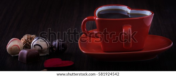 top view image of colorful heart shape chocolates, fabric heart, v cup of coffee on wooden table. valentine's day celebration concept.
