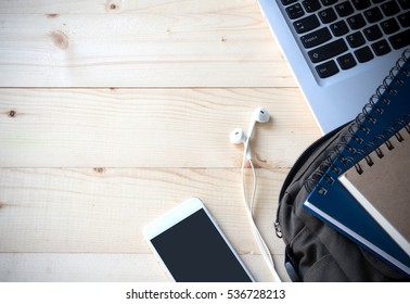 top view image of computer notebook , smart phone , ear phone ,books and shoulder bag , student equipment on desktop concept