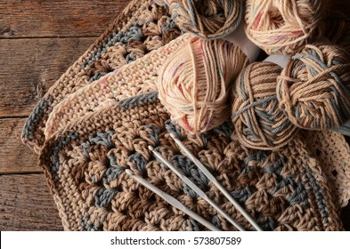 A top view image of crochet yarn, crochet hooks, and hand made granny squares.