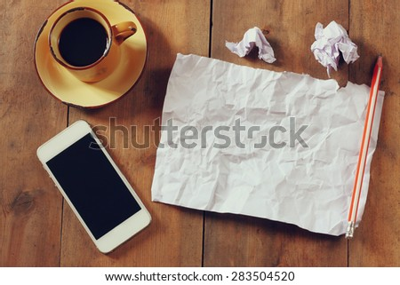 top view image of crumpled blank paper, cup of coffee and smartphone over wooden table