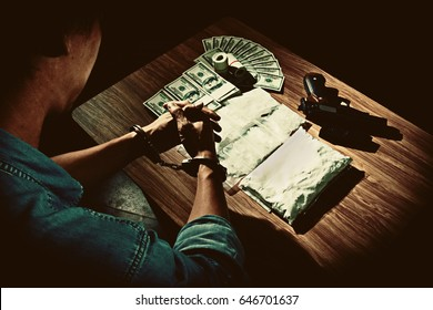 Top view image of the drug dealer was arrested in handcuffs, has stack of banknote, gun and package  powder of drugs on wooden table, Drugs concept in dark vintage color style