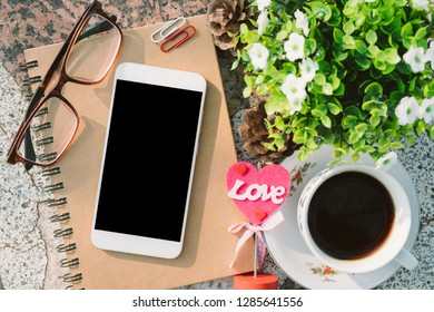 Top view image of empty notebook,smartphone,spectacles and cup of coffee on Marble floor background. Love concept with heart desktop,Valentine's Day.