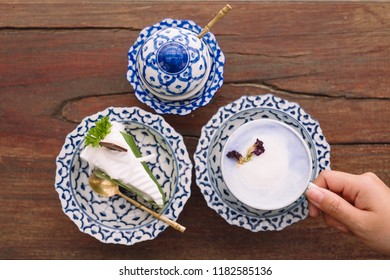 Top view image of a hand holding a cup of hot milk with a piece of cake in an antique Thai traditional benjarong style containers
