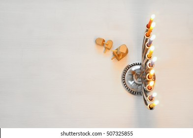 Top view Image of jewish holiday Hanukkah with menorah (traditional Candelabra) and wooden dreidel (spinning top). Selective focus