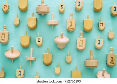 Top view Image of jewish holiday Hanukkah with wooden dreidels colection (spinning top).