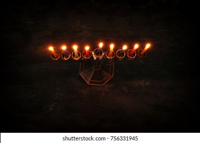 Top view image of jewish holiday Hanukkah background with menorah (traditional candelabra) and burning candles