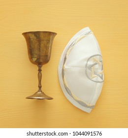 Top view image of jewish wine cup for wine next to Kippah yarmulke (hat). passover holiday and shabbat concept.