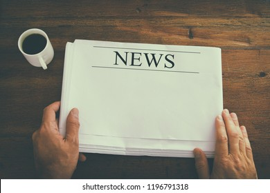 top view image of male hand holding blank Newspaper with empty space to add news or text. retro style image