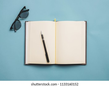 Top view image of notebook with glasses on blue background.