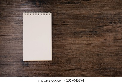 Top view image of open notebook with blank page on the wooden table.