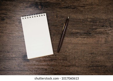 Top view image of open notebook with blank page and pen on the wooden table.