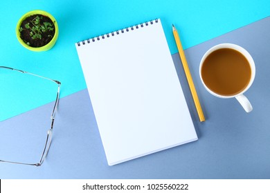 Top view image of open notebook with blank pages and coffee on blue background, ready for adding or mock up. Still life, business, office supplies or education concept. Notepad. Note paper.