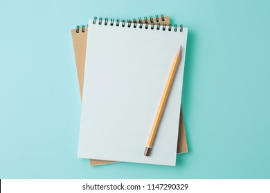 Top view image of  open notebook with blank pages. school notebook on a cyan background, spiral notepad on a table